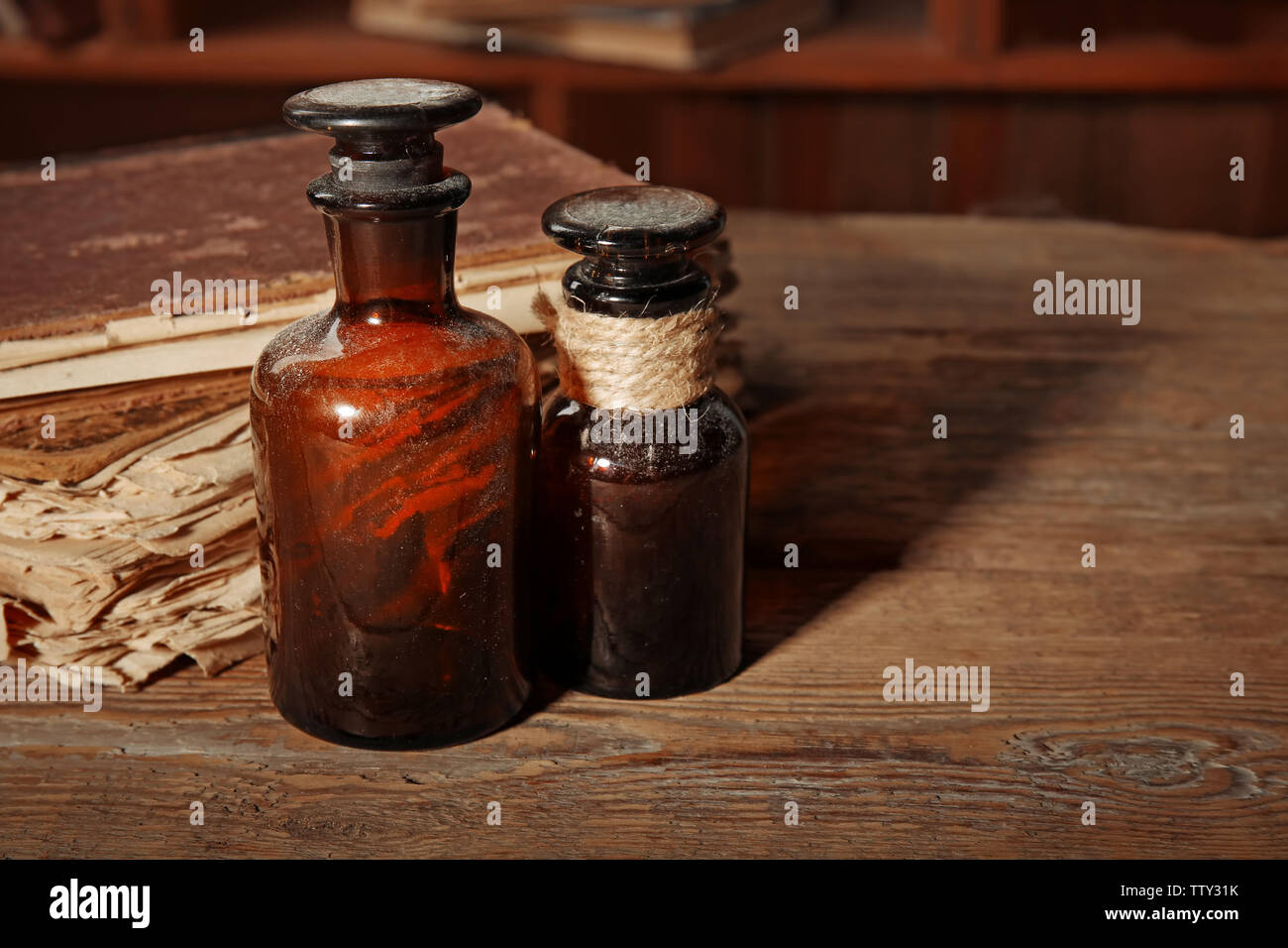 Vintage glass bottles with old books on wooden table, closeup - Stock Image