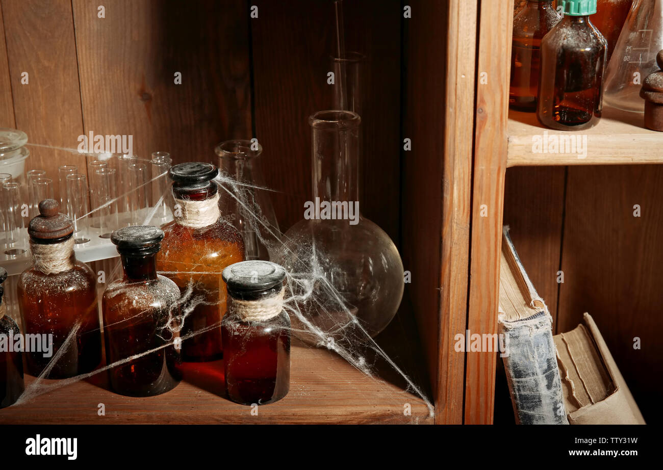 Vintage glass bottles with spiderweb on wooden shelf, closeup - Stock Image