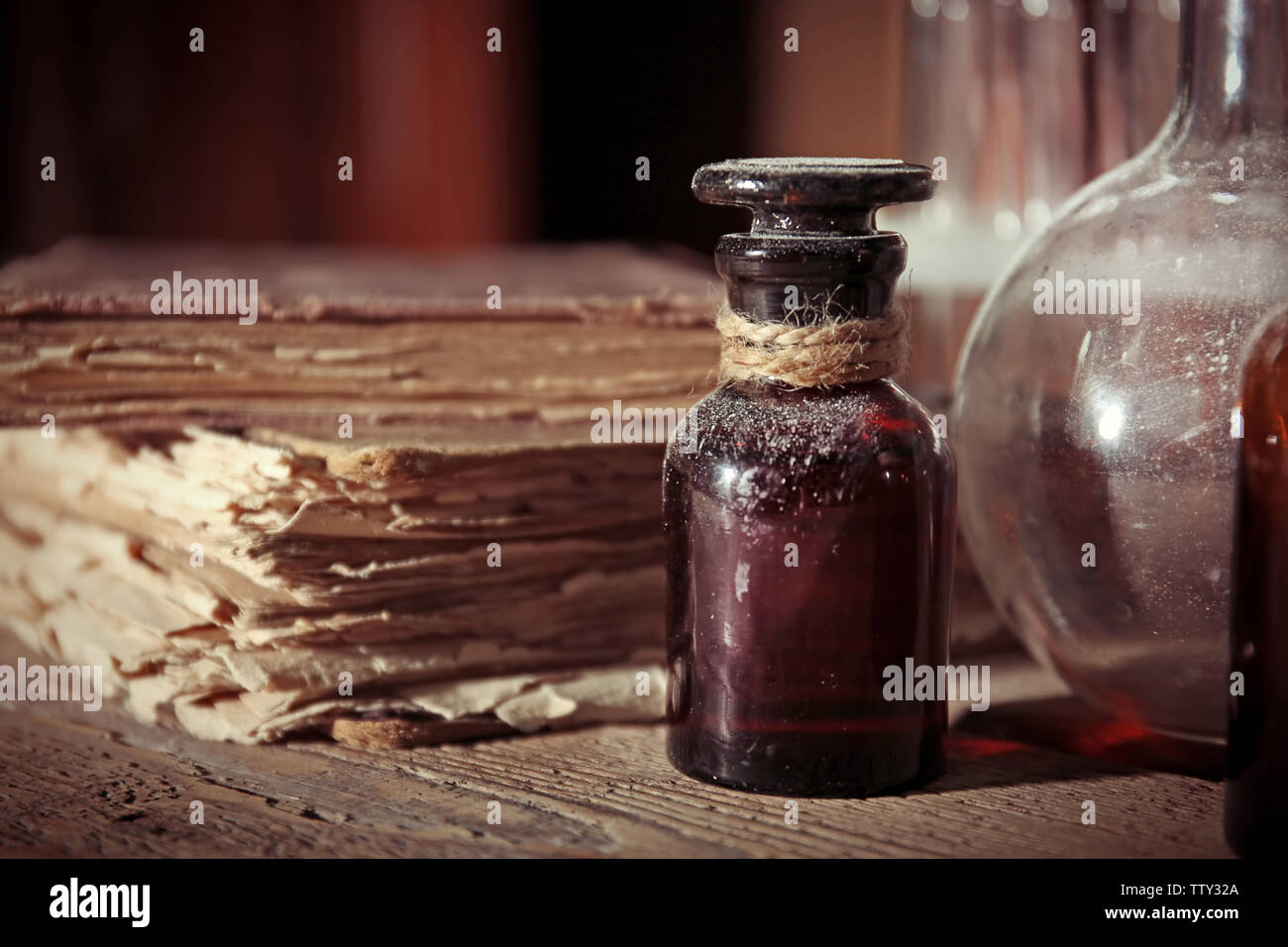 Vintage glass bottle with old books on wooden table, closeup - Stock Image