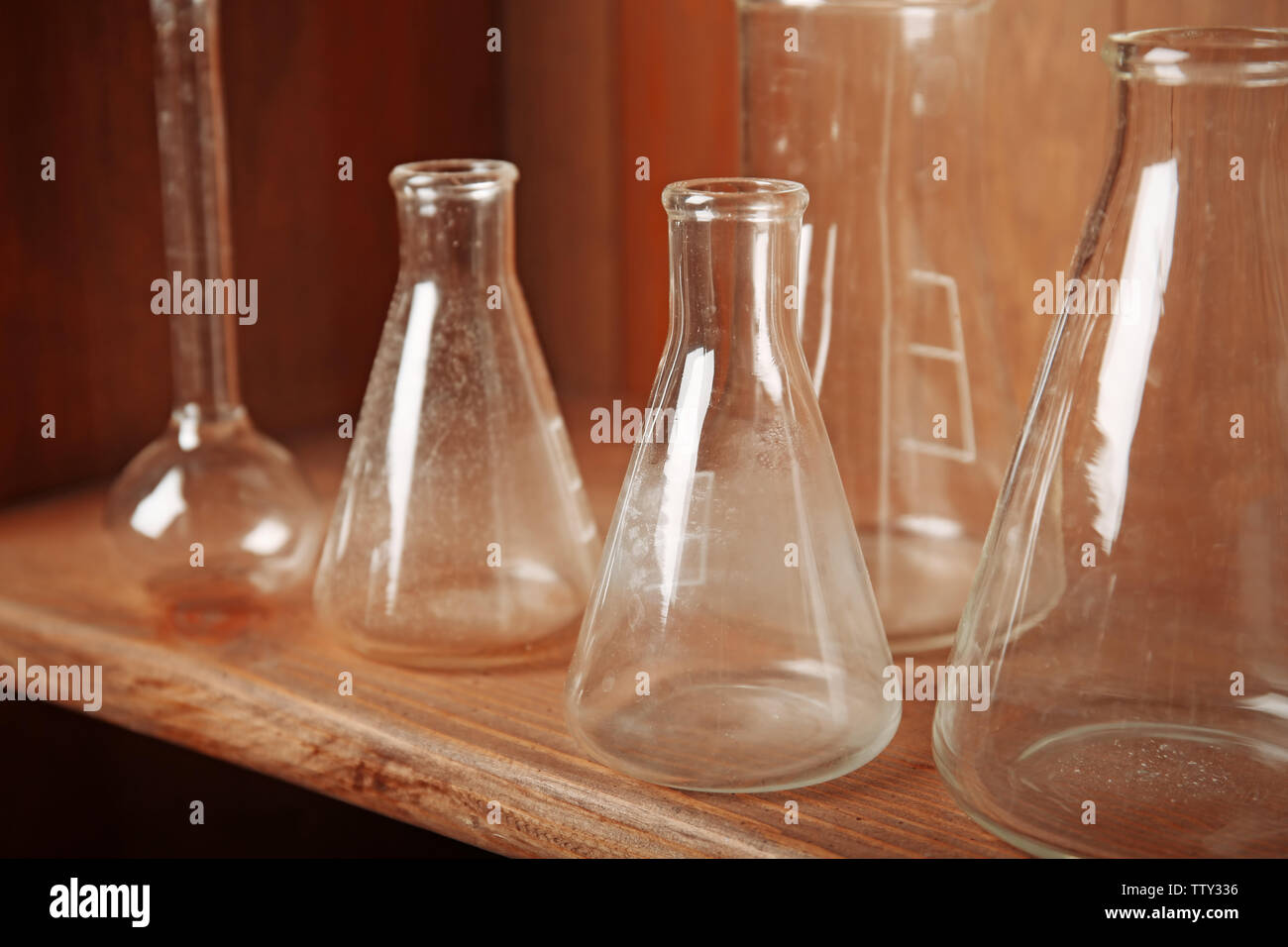 Vintage equipment of chemical laboratory on wooden shelf, closeup - Stock Image