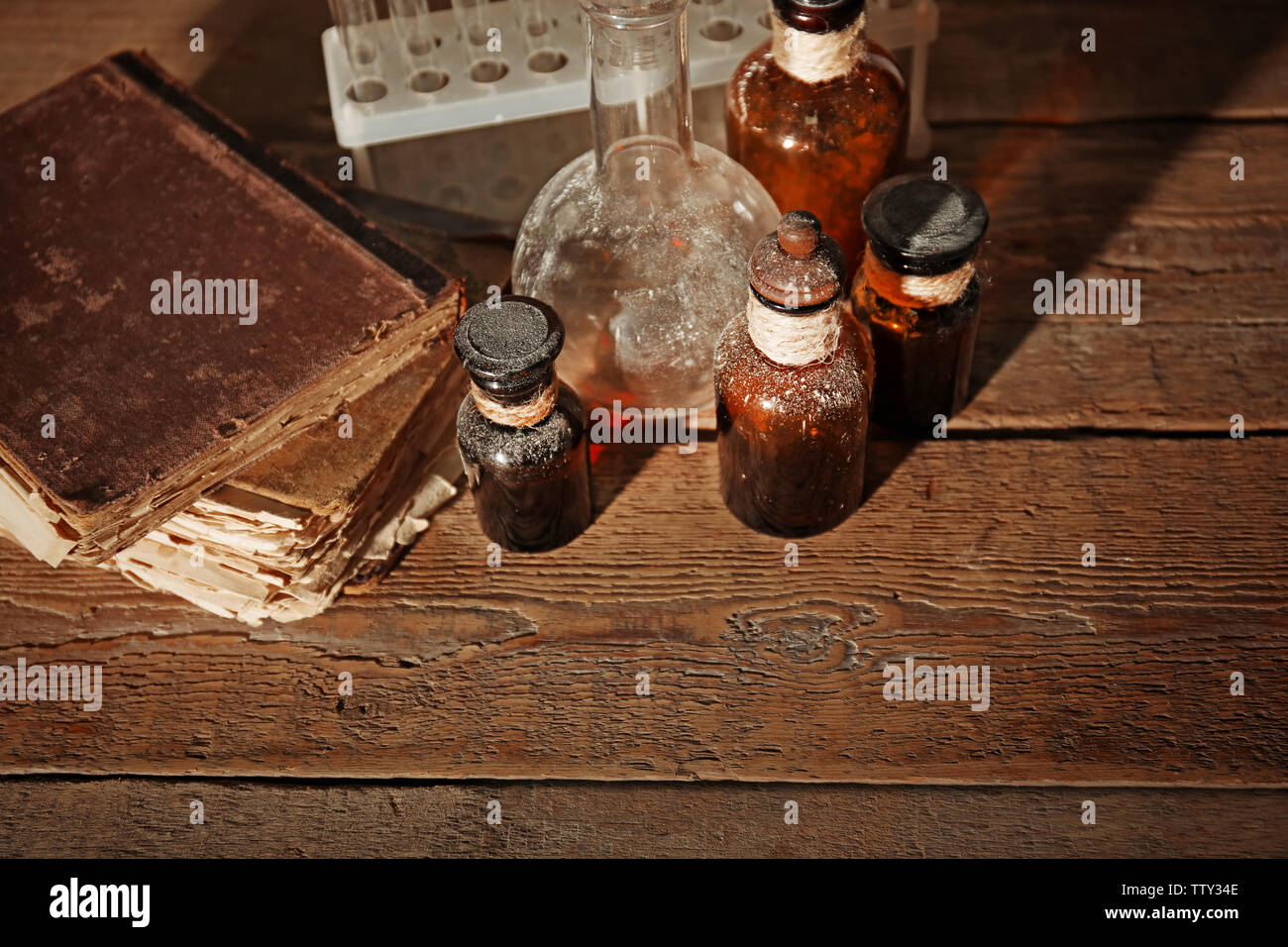 Vintage glass bottles with flask on wooden background, closeup - Stock Image