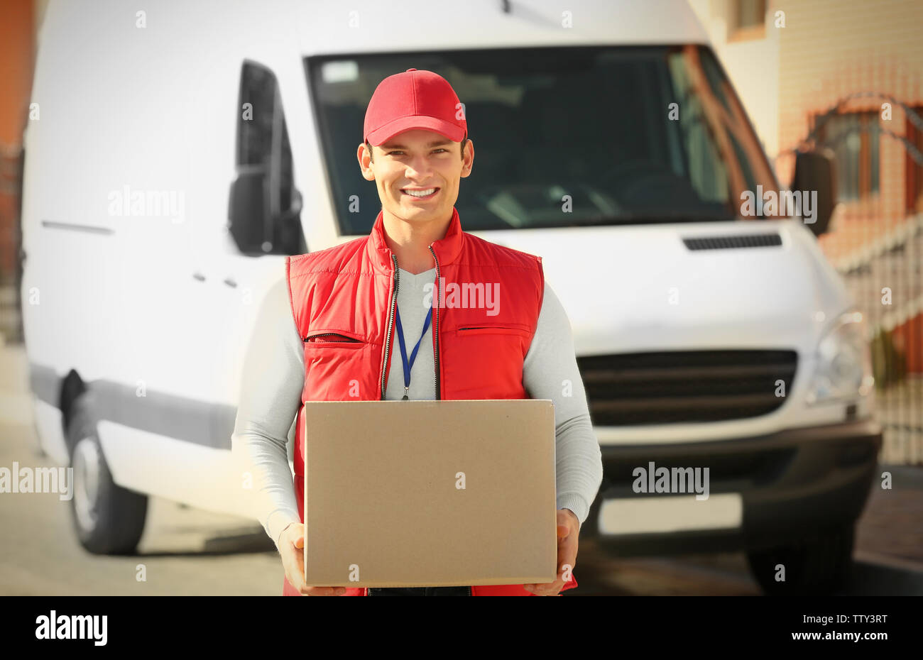 Young male courier with parcel outdoor - Stock Image