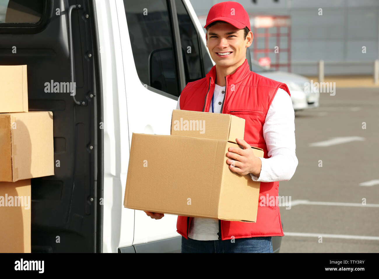 Young male courier with parcels near delivery service van - Stock Image