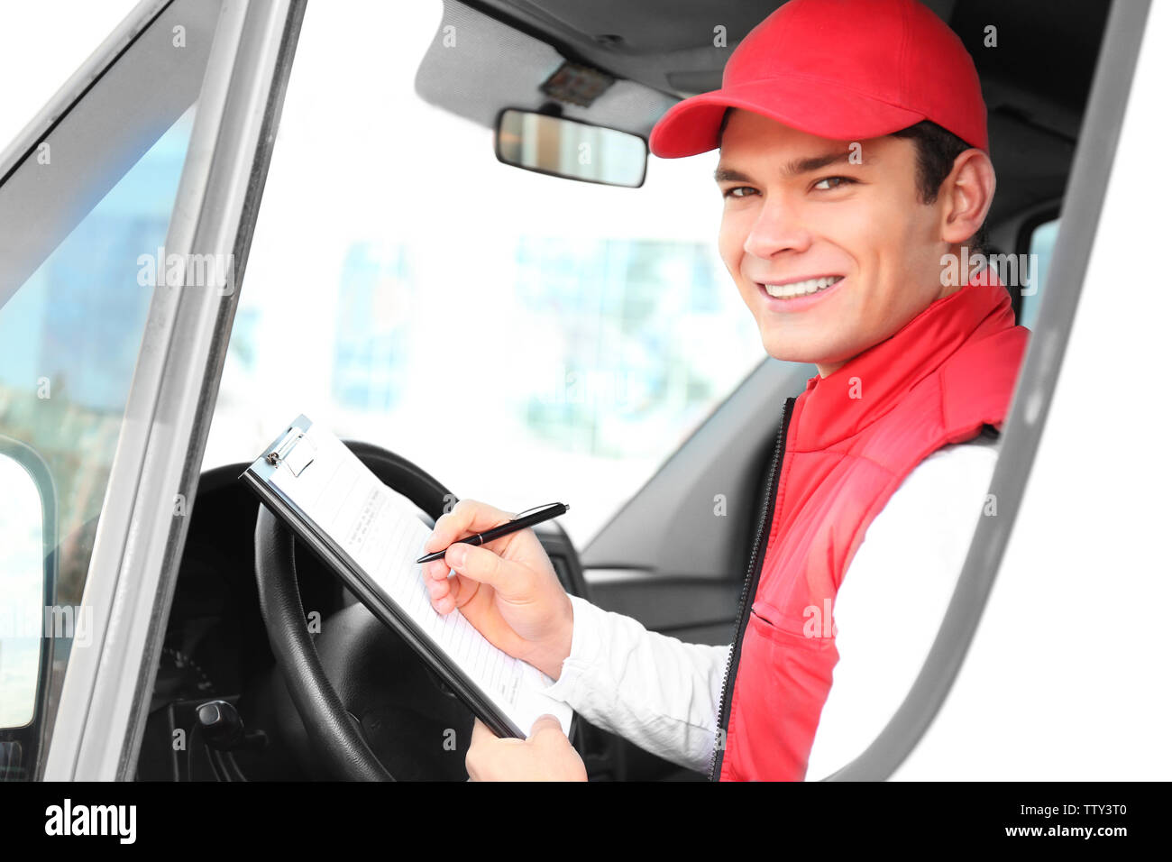 Young male courier with clipboard in delivery service van - Stock Image