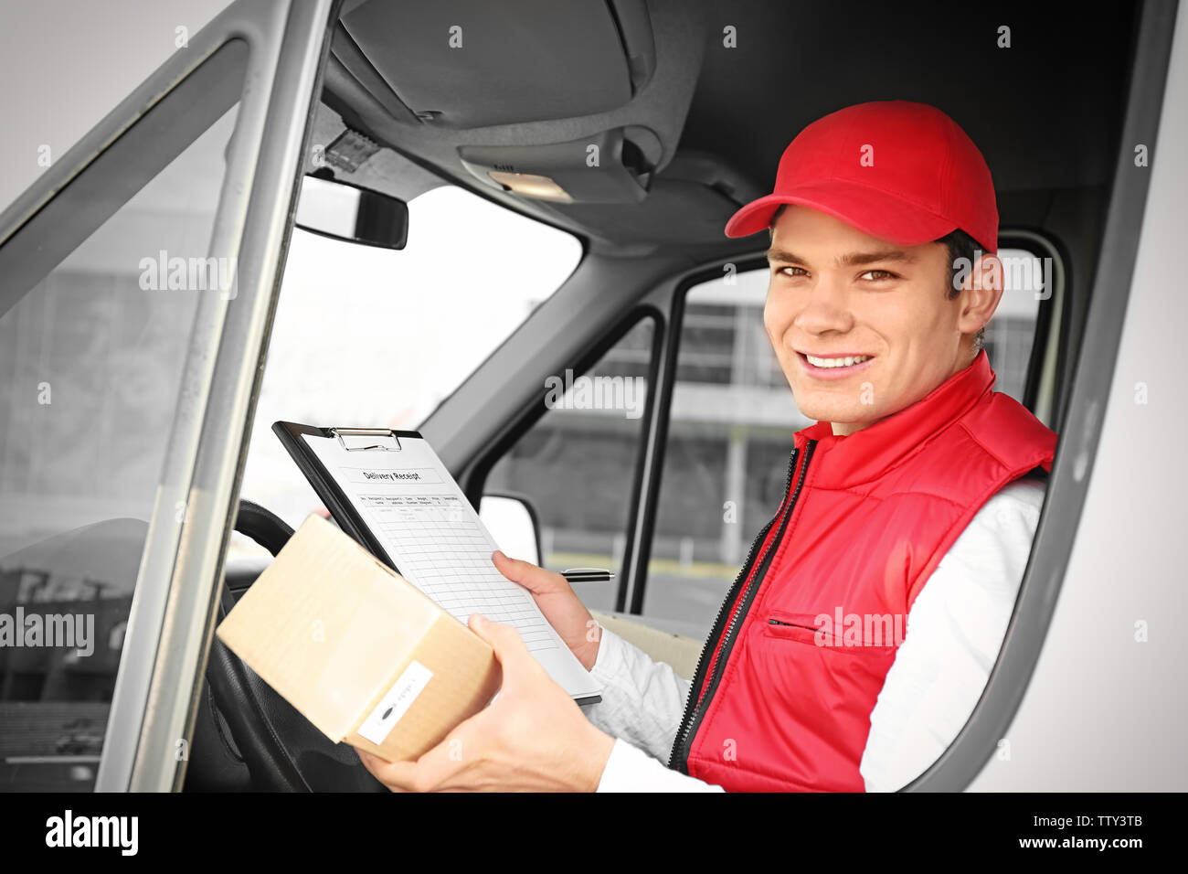 Young male courier with clipboard and parcel in delivery service van - Stock Image