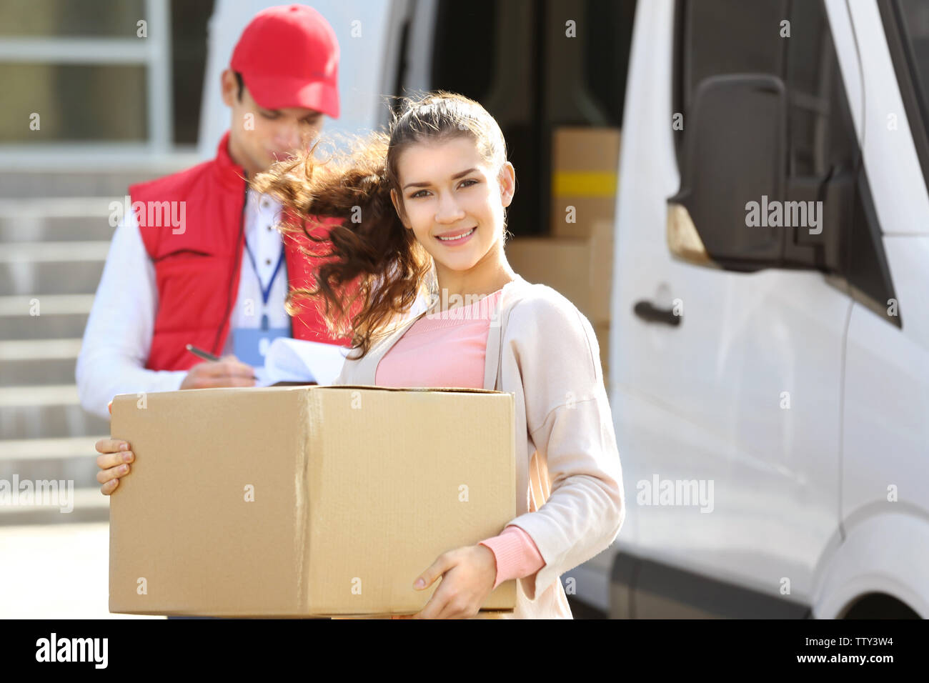 Young woman with parcel and male courier near delivery service van - Stock Image