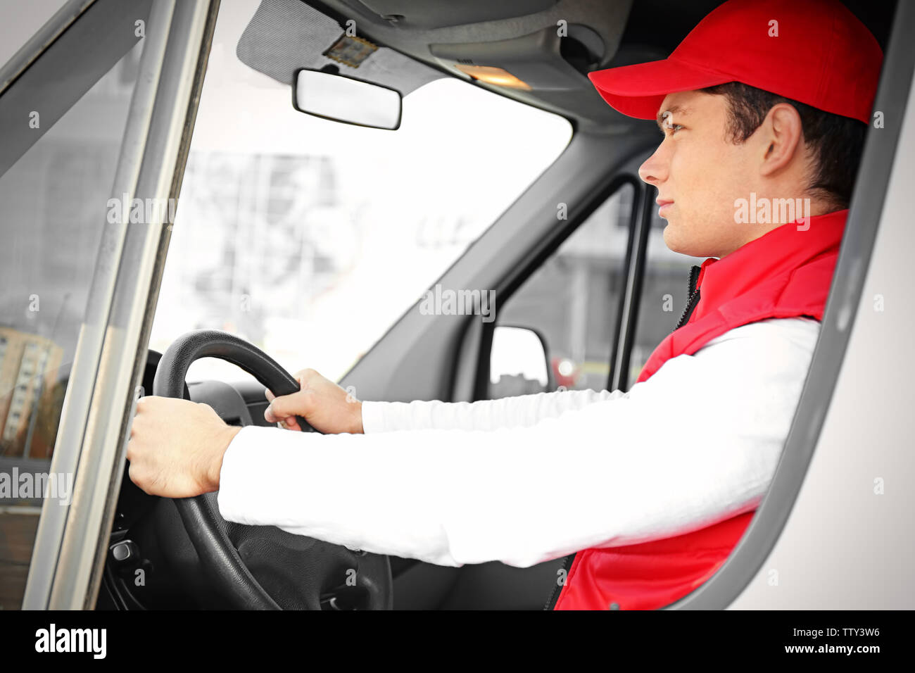 Young male courier driving delivery service van - Stock Image