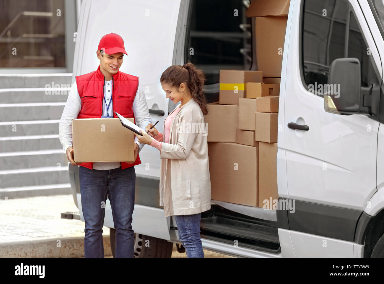 Young woman signing receipt for delivering parcel from male courier - Stock Image