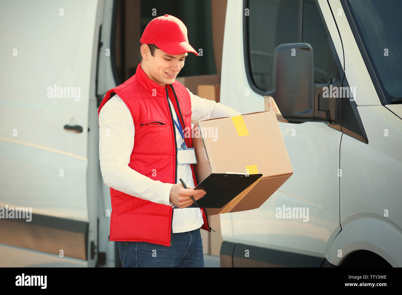 Young male courier with clipboard and parcel near delivery service van - Stock Image