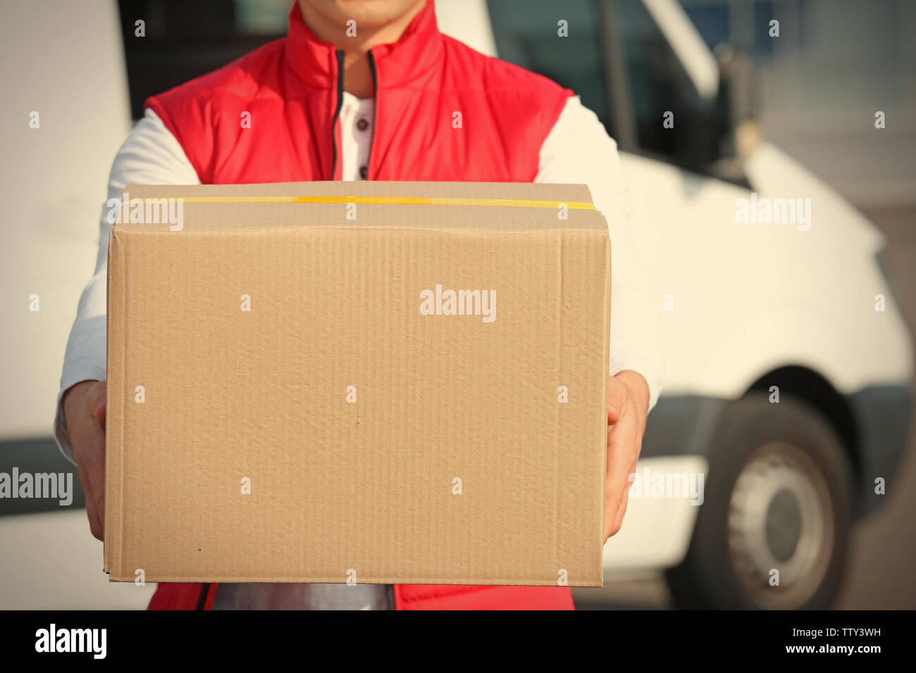 Young male courier with parcel, closeup - Stock Image