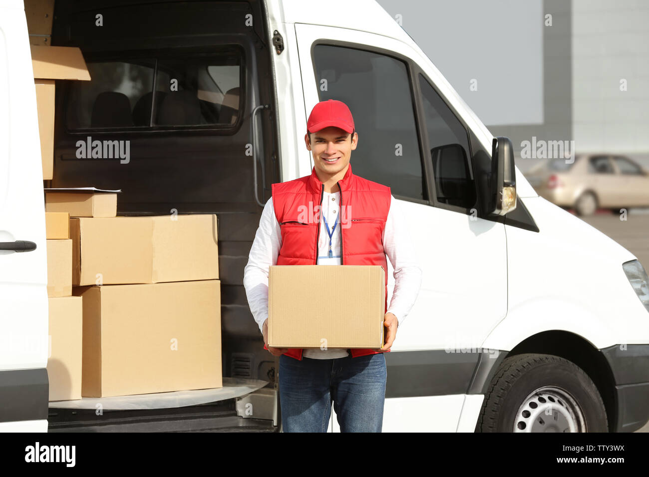 Young male courier with parcel near delivery service van - Stock Image