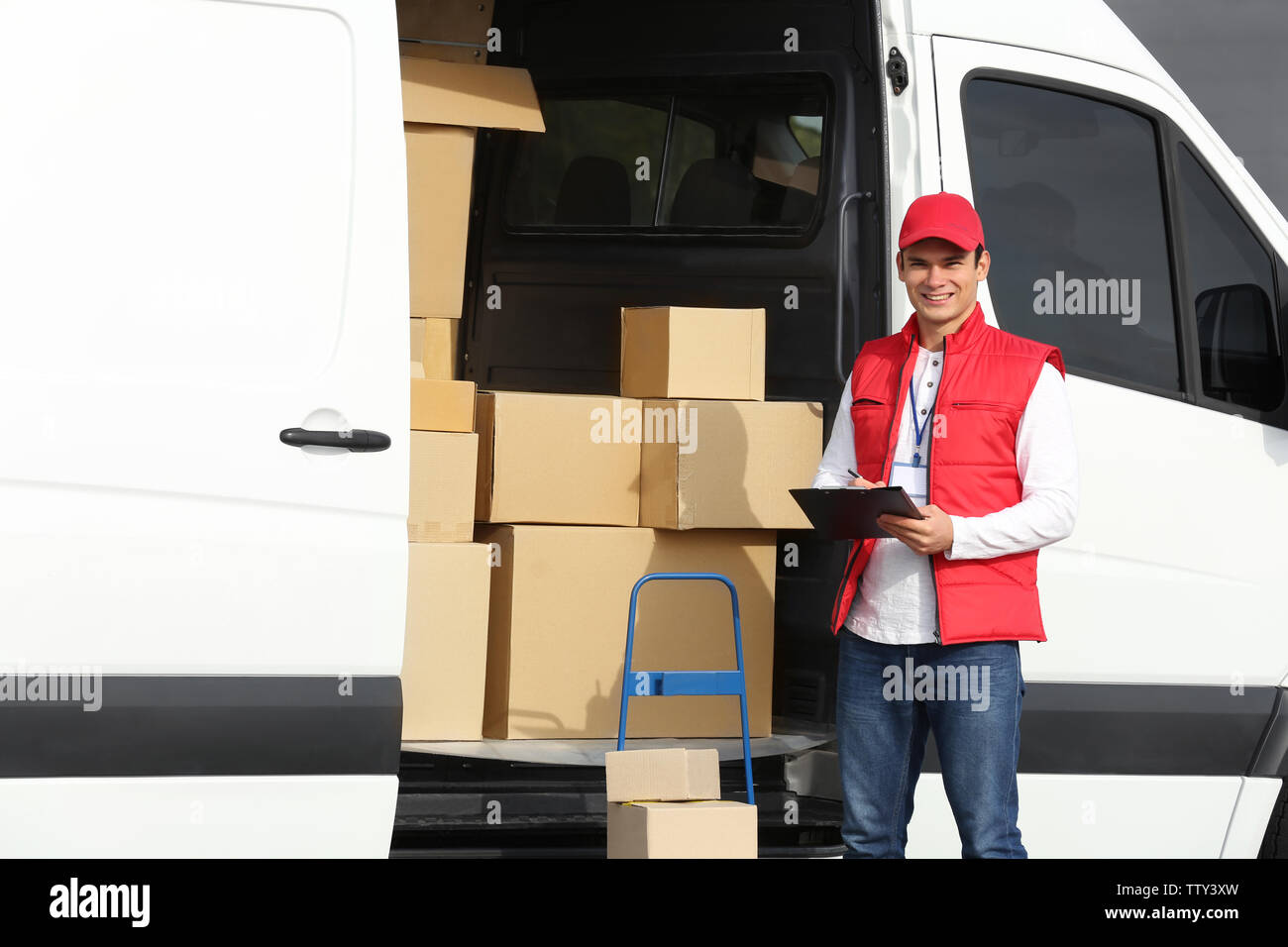 Young male courier with clipboard near delivery service van - Stock Image