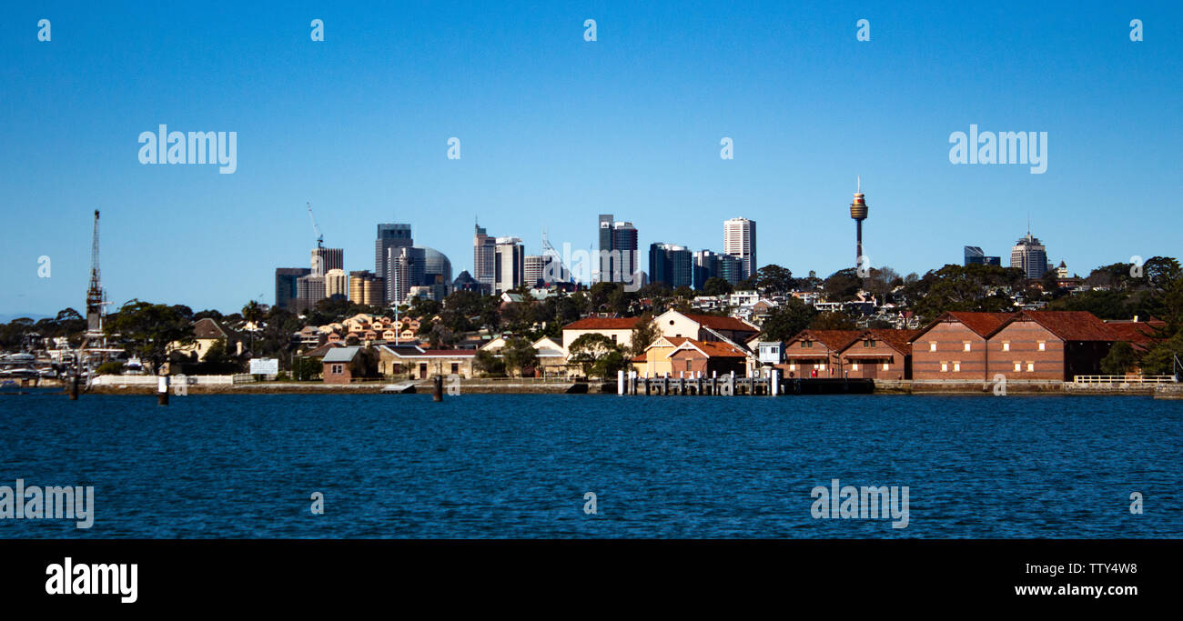 City Harbourside houses, wharf and boat sheds on Sydney Harbour with city CBD skyline in background against blue sky - Stock Image