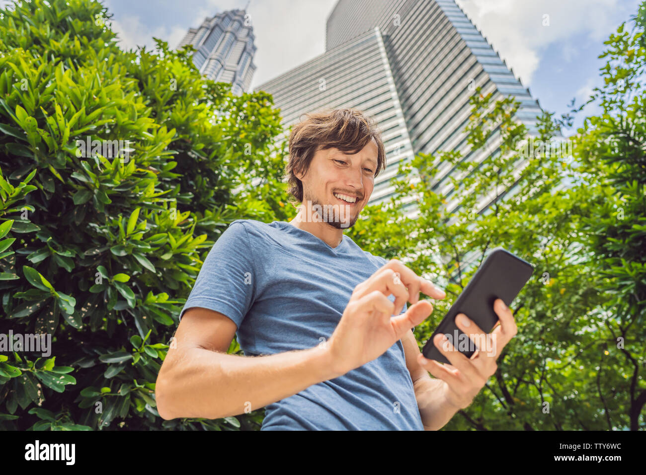 Man Tourist using navigation app on the mobile phone. Navigation map on a smartphone in a big city Stock Photo