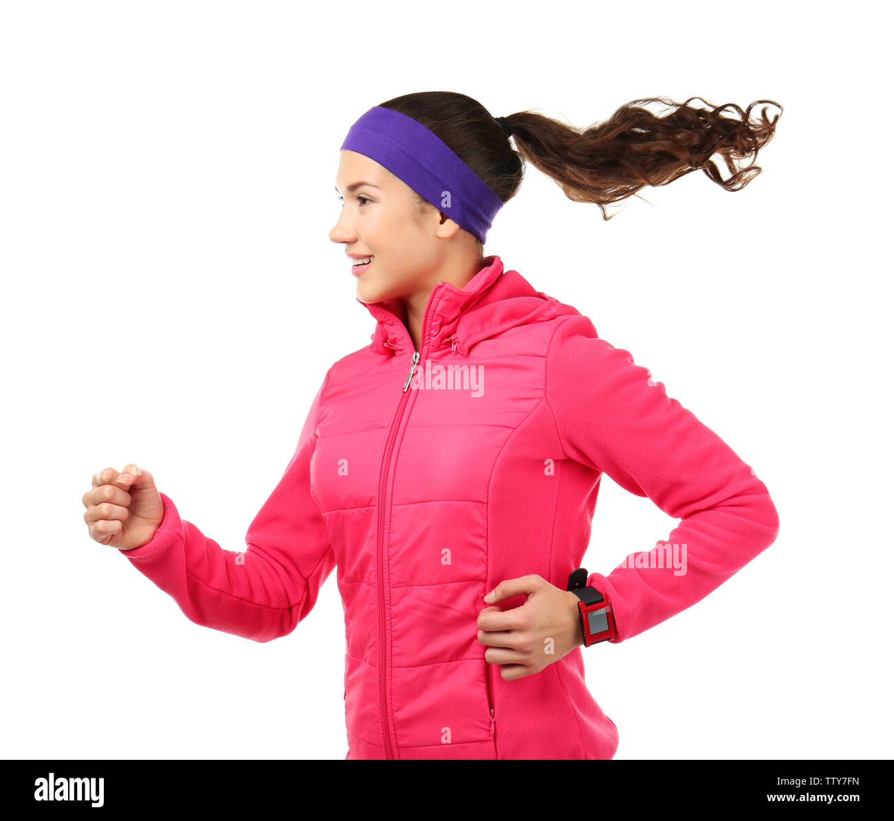 Running young woman in warm clothes on white background - Stock Image