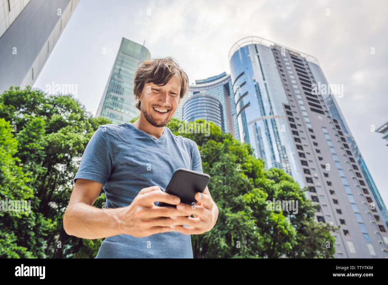Man Tourist using navigation app on the mobile phone. Navigation map on a smartphone in a big city - Stock Image
