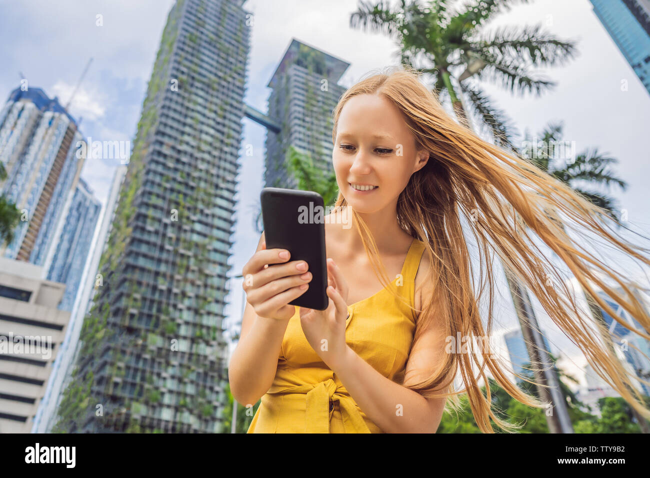 Woman Tourist using navigation app on the mobile phone. Navigation map on a smartphone in a big city - Stock Image