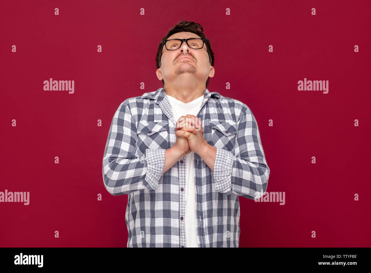 Oh god please help me. Portrait of hopeful sad worry middle aged man in casual checkered shirt and eyeglasses standing, praying and looking at up. ind - Stock Image