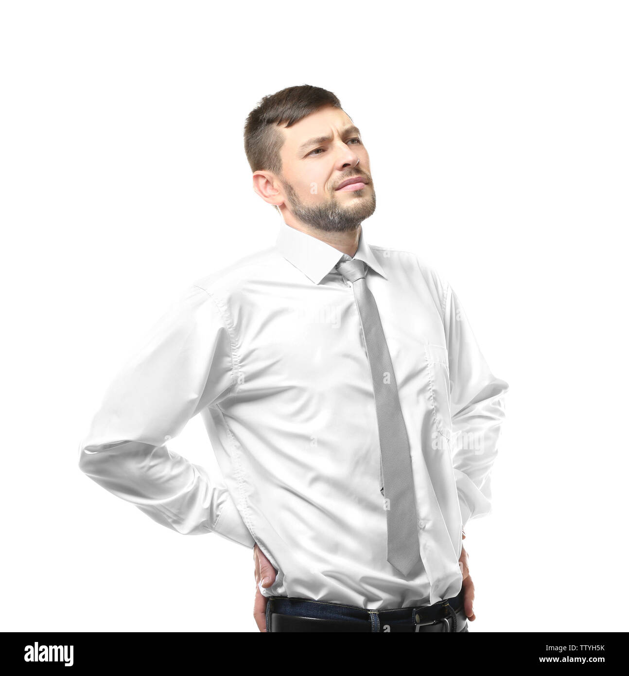 Young man with back pain on white background - Stock Image