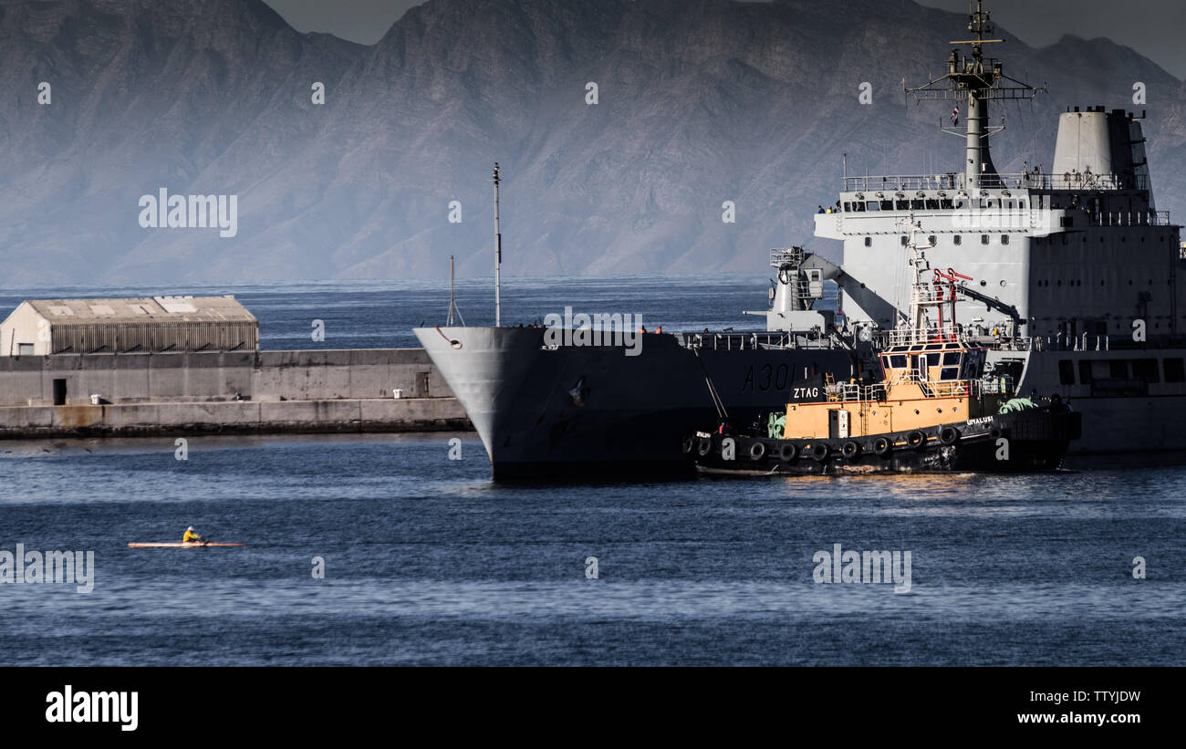 The SAS Drakensberg fleet replenishment ship at the Simons Town naval base in the Western Cape, South Africa, with a man rowing a skull - Stock Image