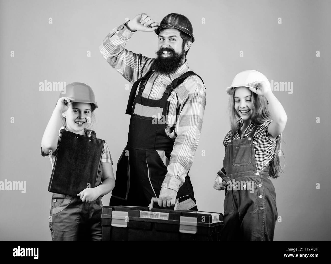 construction worker assistant. Builder or carpenter. Repairman in uniform. Engineer. Bearded man with little girls. Repair. Childrens creativity. Father and daughter in workshop. Confidence at safety. - Stock Image