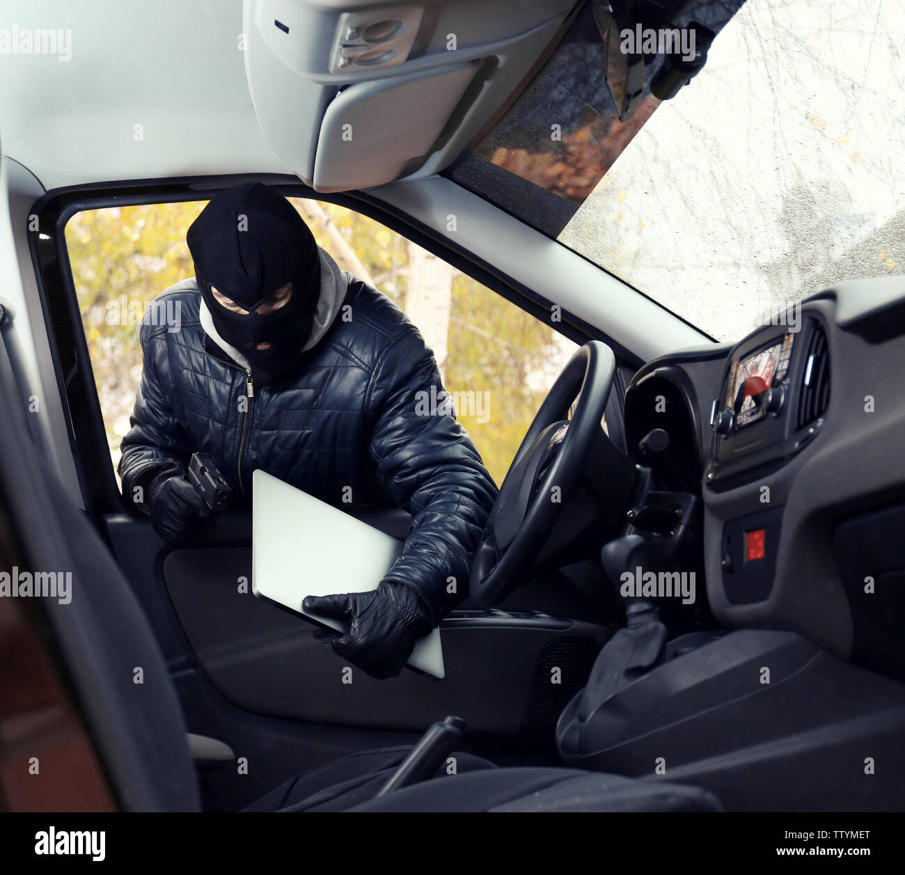 Thief in mask stealing laptop from a car - Stock Image