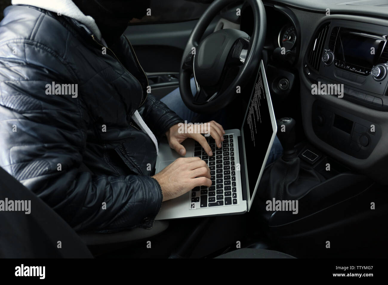 Car thief hacking security systems with laptop computer - Stock Image