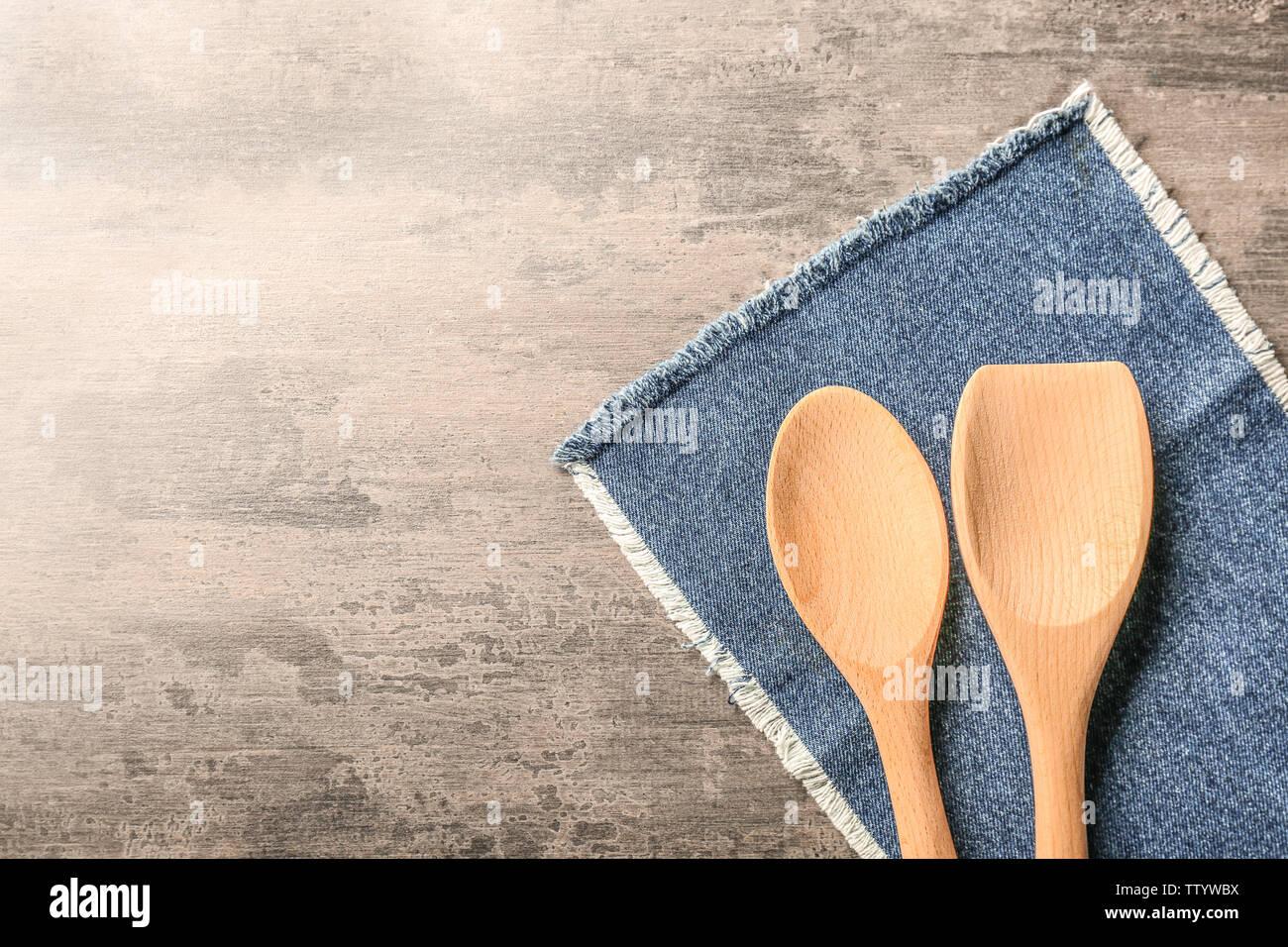 Wooden kitchen utensils with denim napkin on table - Stock Image