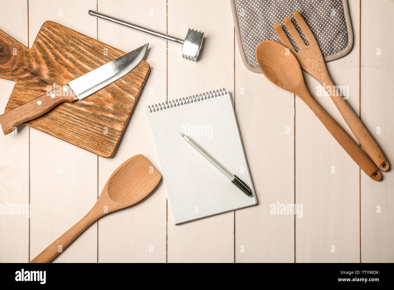 Kitchen utensils with empty notebook on wooden table - Stock Image