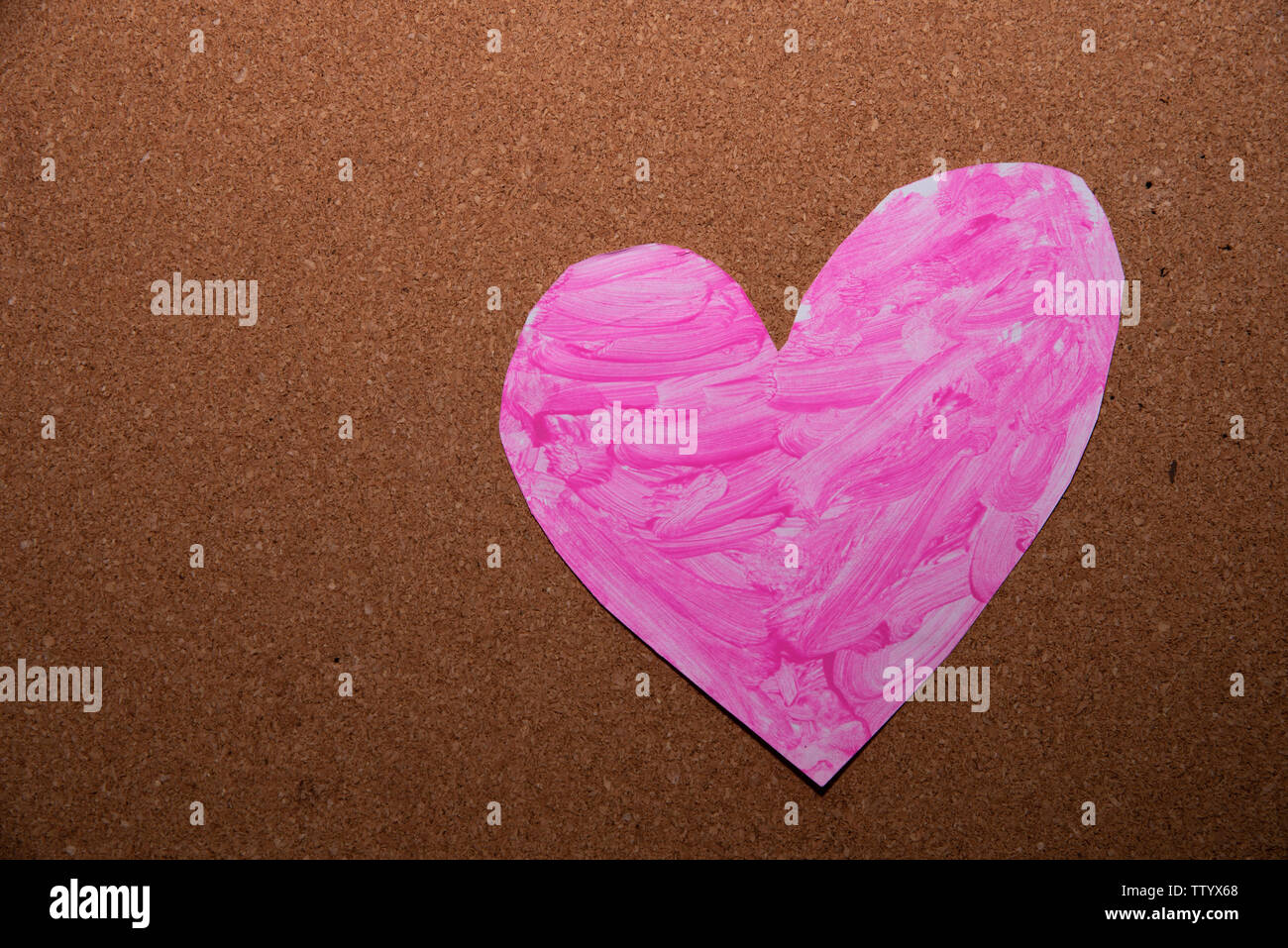 love heart symbol painted pink on a cork board - Stock Image