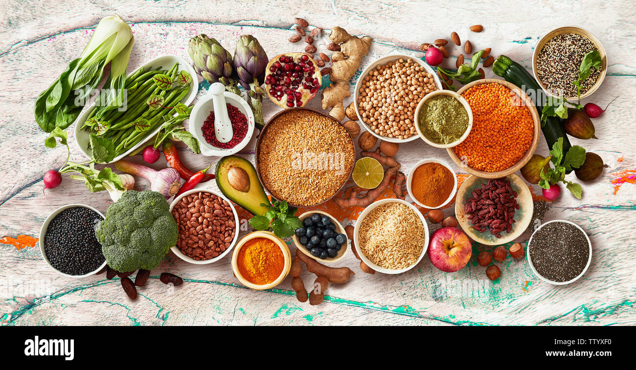 Rustic flat lay panorama of healthy fruit and vegetables with fresh produce, dried legumes and seeds and bowls of cereals viewed from above in a conce Stock Photo