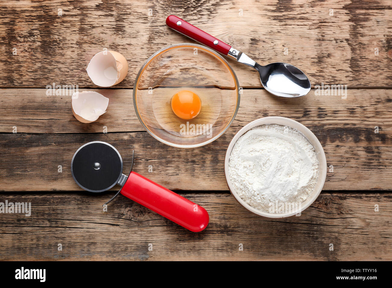 Food ingredients and kitchen utensils for cooking on wooden background - Stock Image