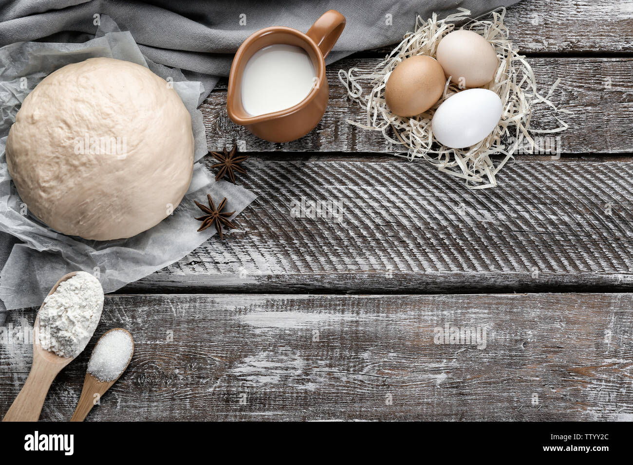 Fresh dough, eggs and milk on wooden background - Stock Image