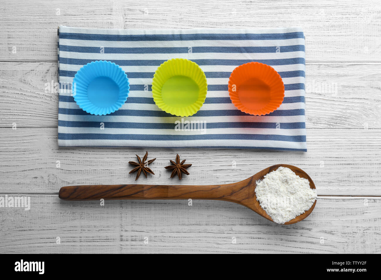 Kitchen molds for baking and spoon with flour on wooden background - Stock Image