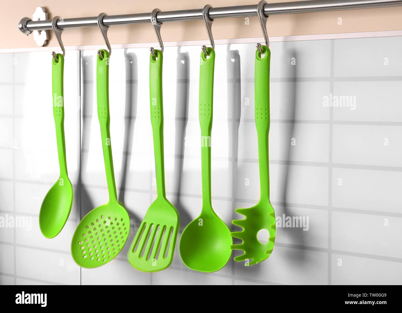 Set of kitchen utensils hanging on the wall - Stock Image
