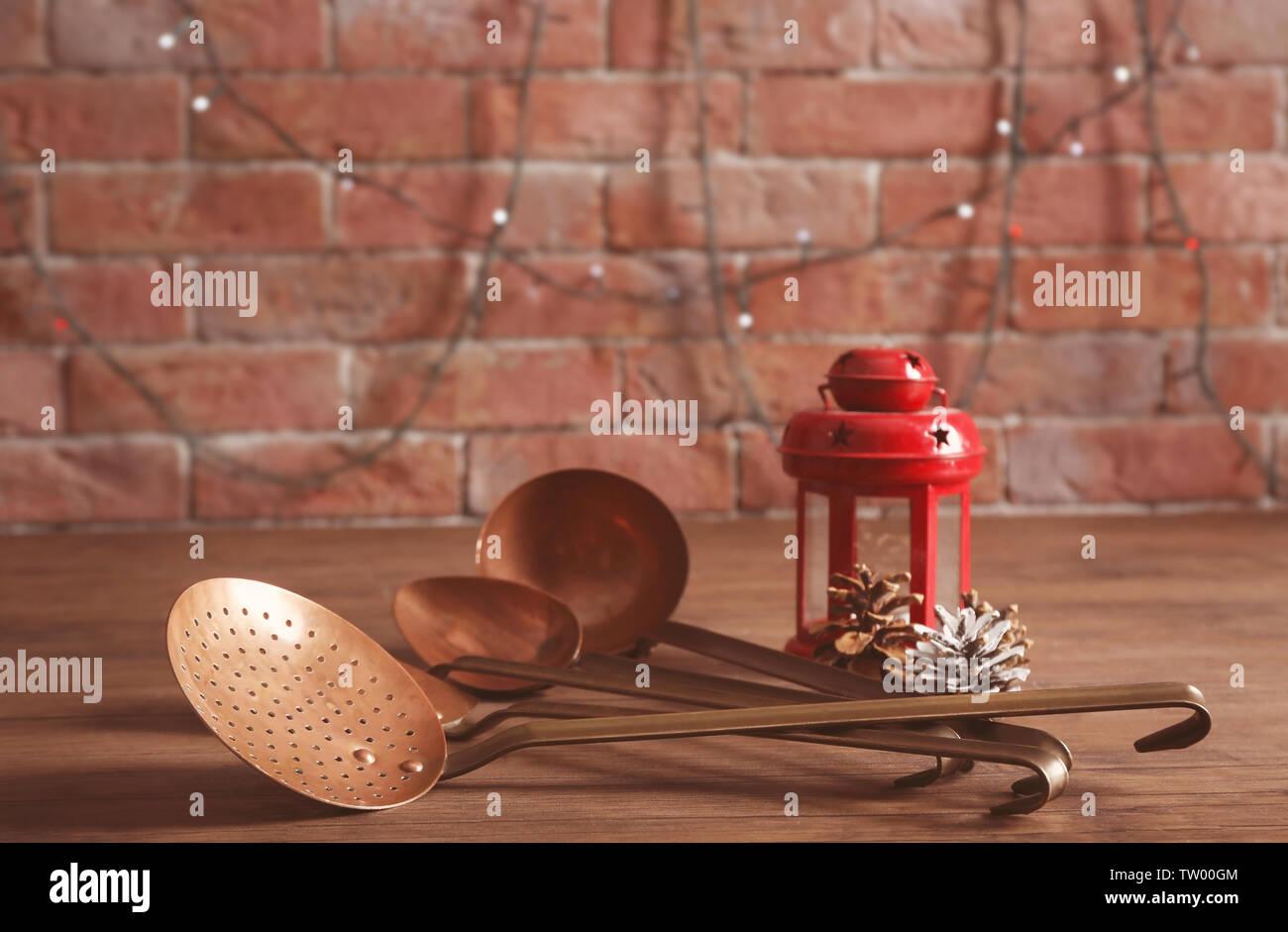 Set of metal kitchen utensils on wooden table - Stock Image