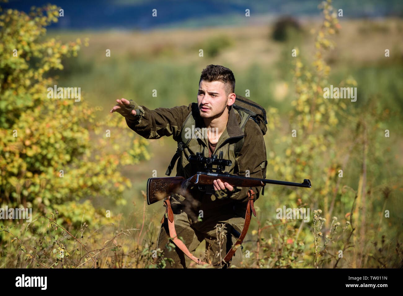 Hunter hold rifle. Man wear camouflage clothes nature background. Hunting permit. Hunting equipment for professionals. Hunting is brutal masculine hobby. Bearded serious hunter spend leisure hunting. - Stock Image