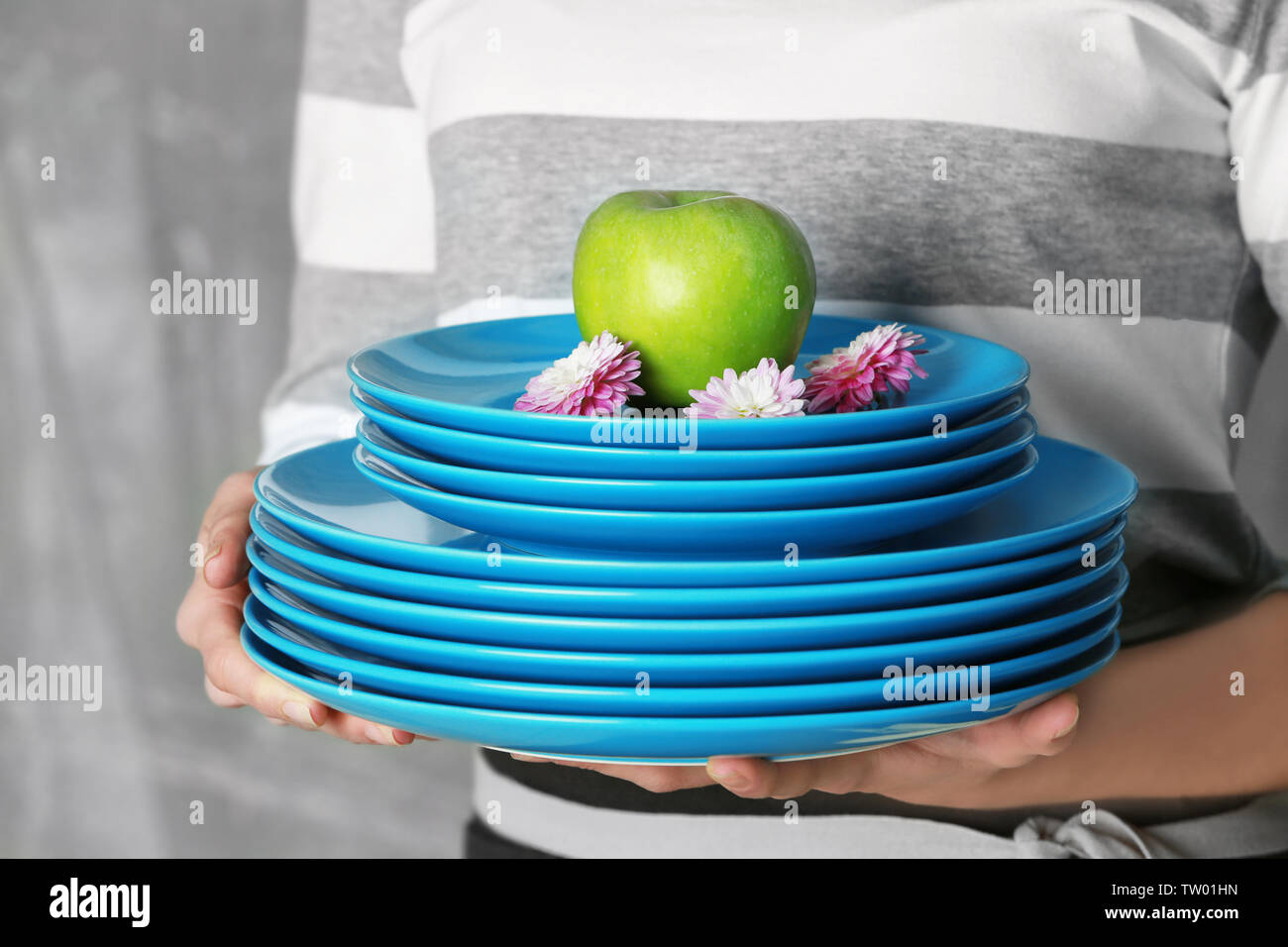 Female hands holding dishes, closeup - Stock Image