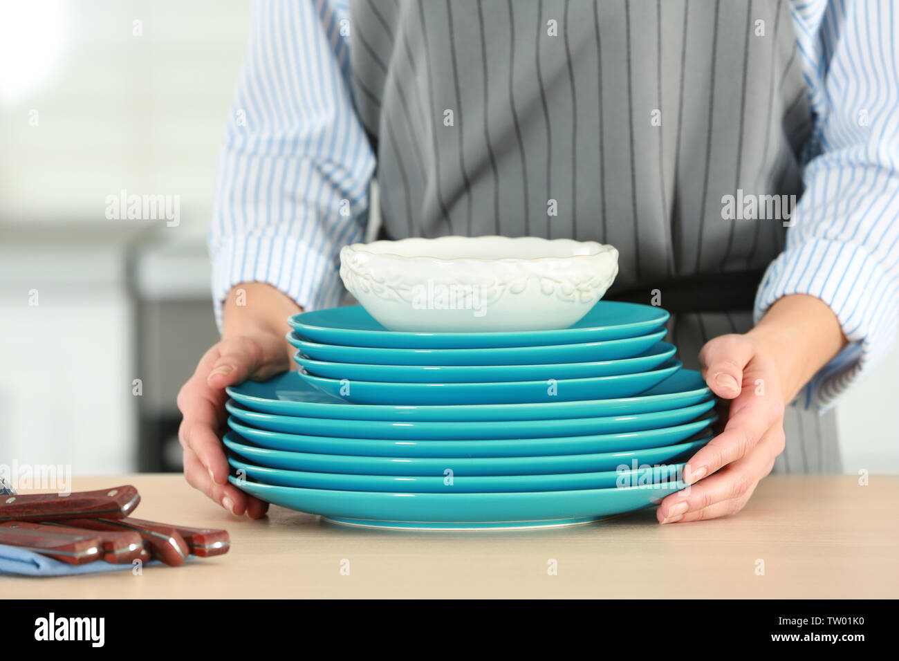 Female hands holding dishes on kitchen counter - Stock Image