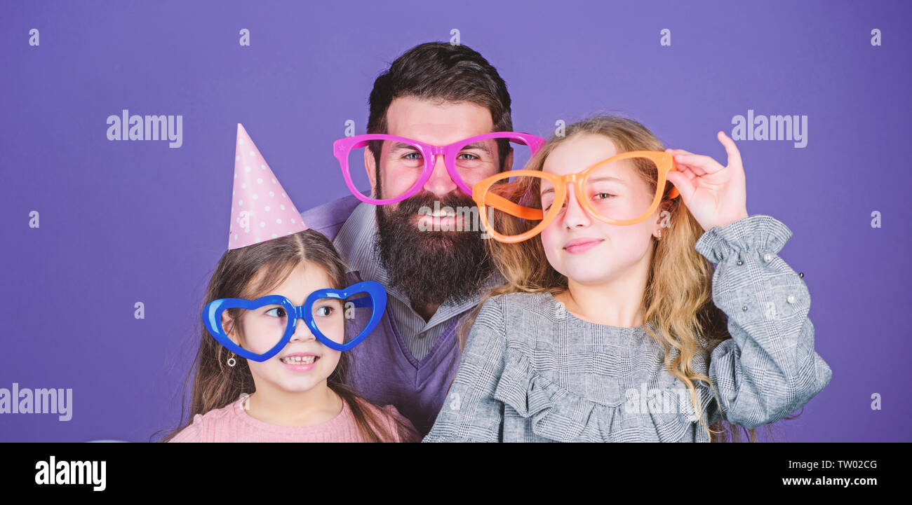 A get together. Family party. Happy family celebrating birthday party. Family of father and daughters wearing party goggles. Father and girl children enjoying party time. Having a family celebration. - Stock Image