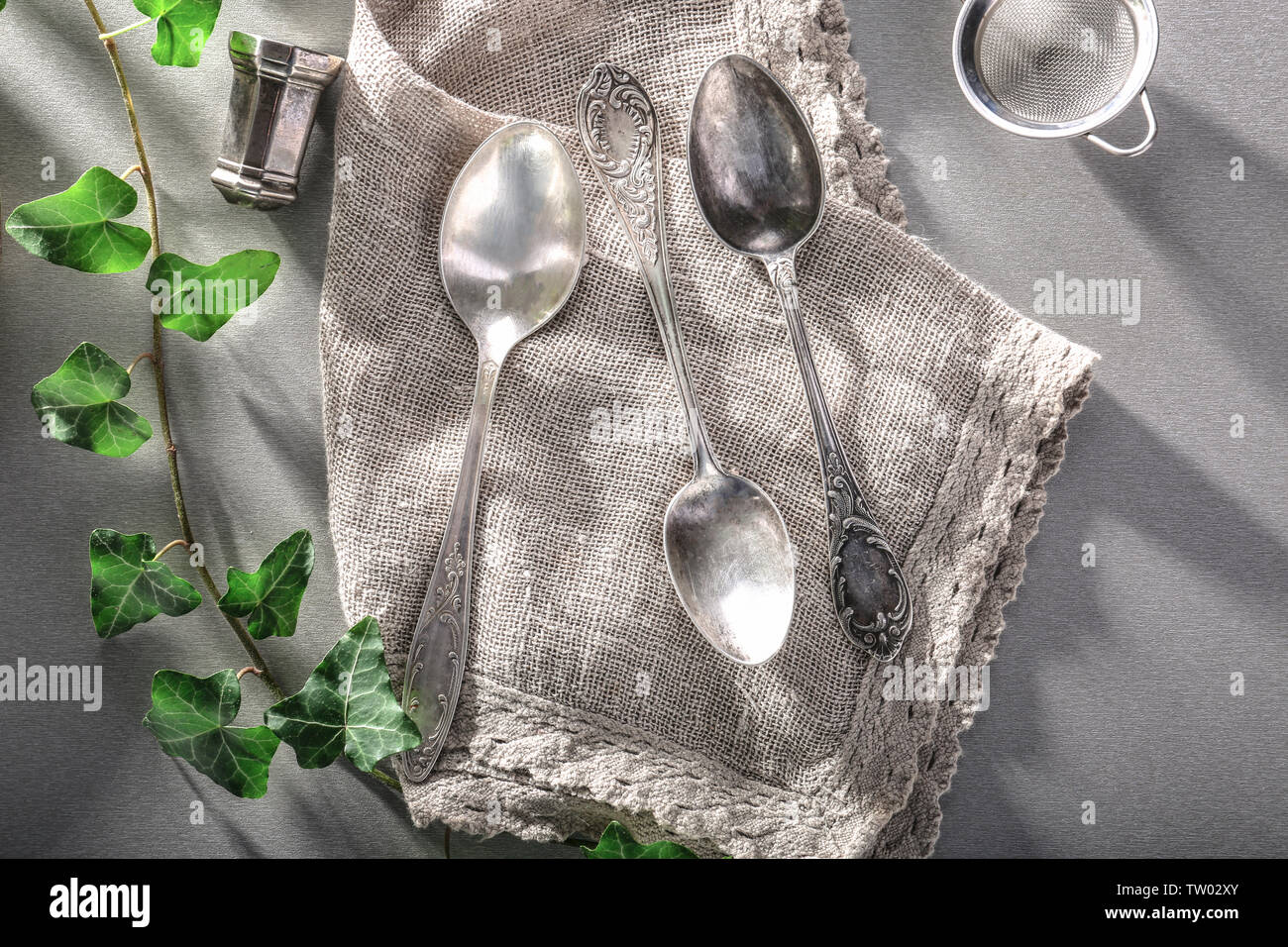 Sackcloth napkin with silverware and ivy on gray background - Stock Image