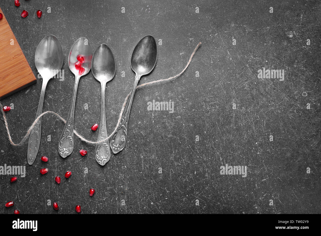 Cutlery set and garnet on gray table - Stock Image