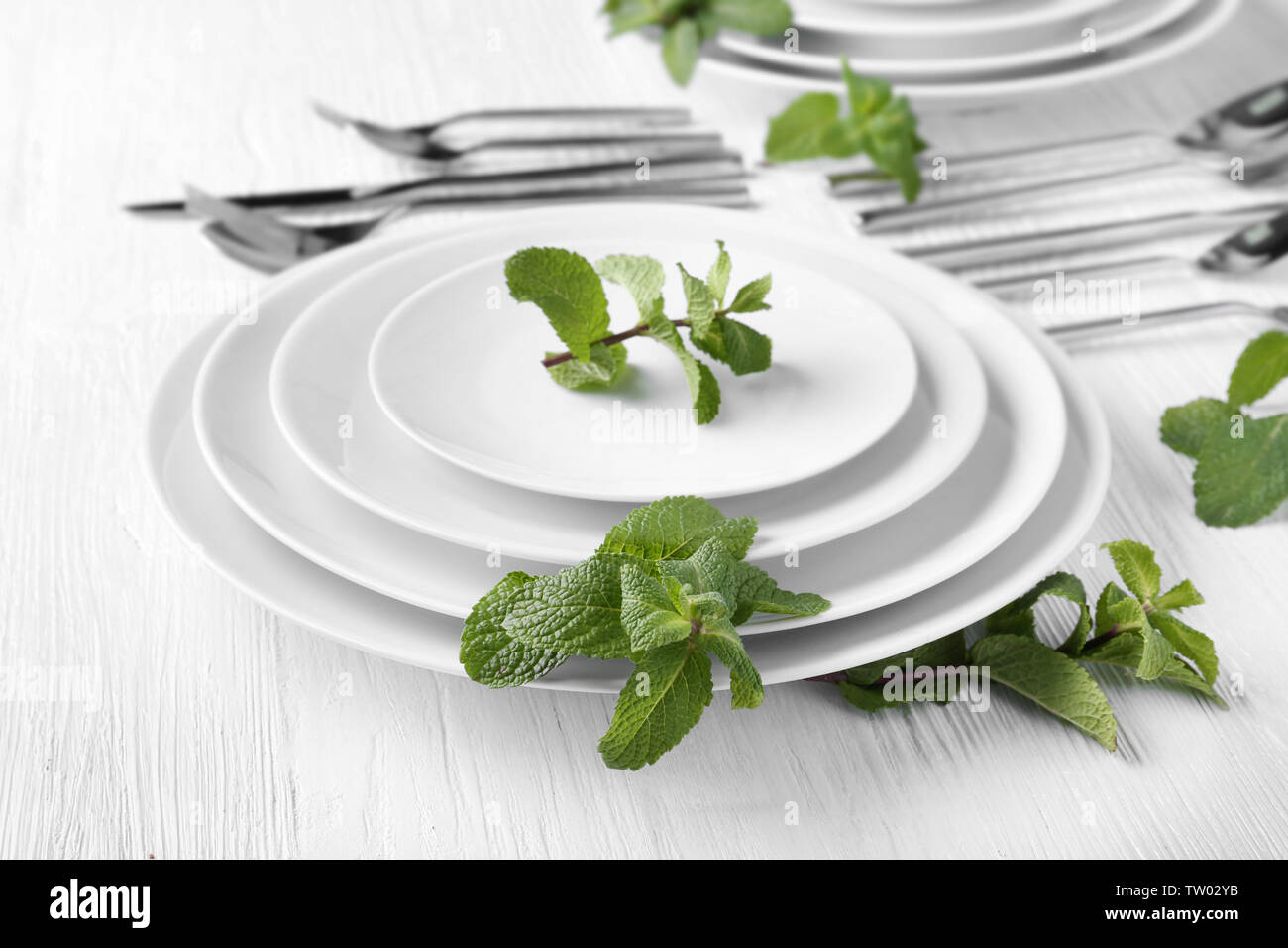 Mint on plates and cutlery set on background - Stock Image