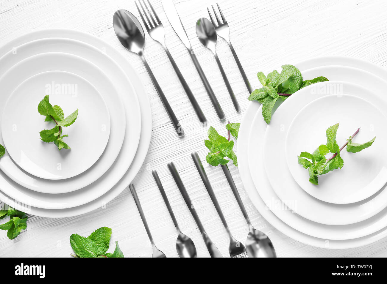 Cutlery set with plates on white wooden table - Stock Image