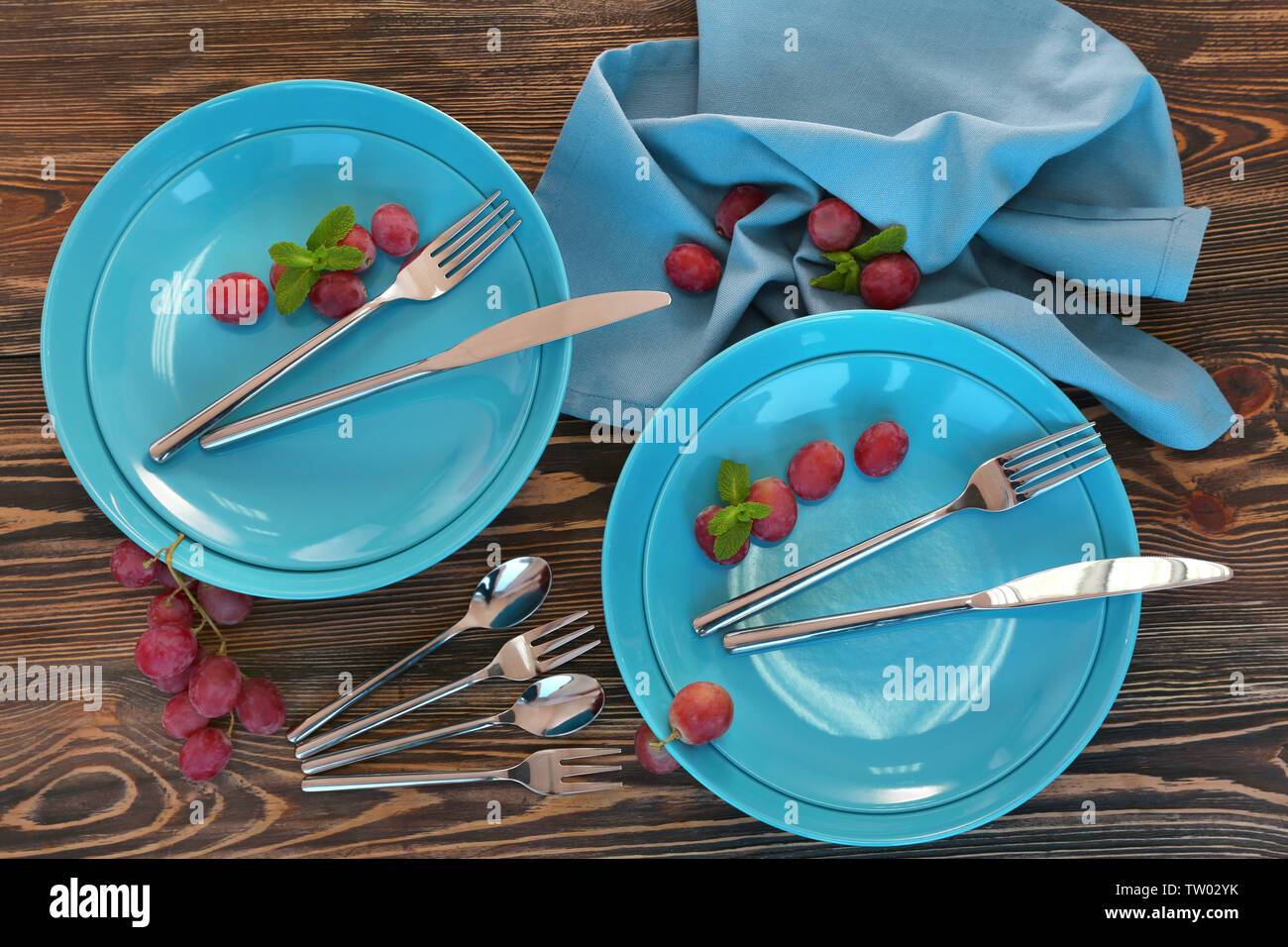 Blue plates and cutlery on wooden background - Stock Image