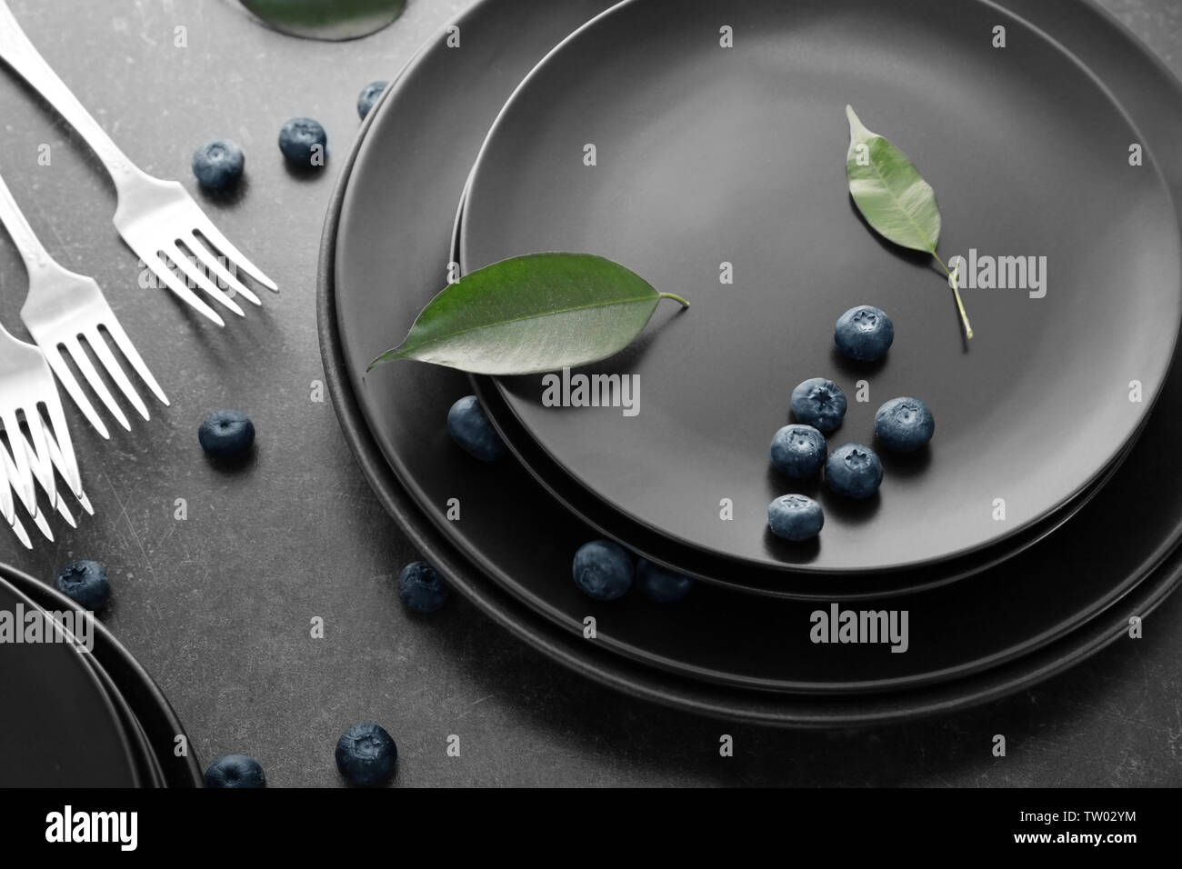 Black plates and cutlery on gray background - Stock Image