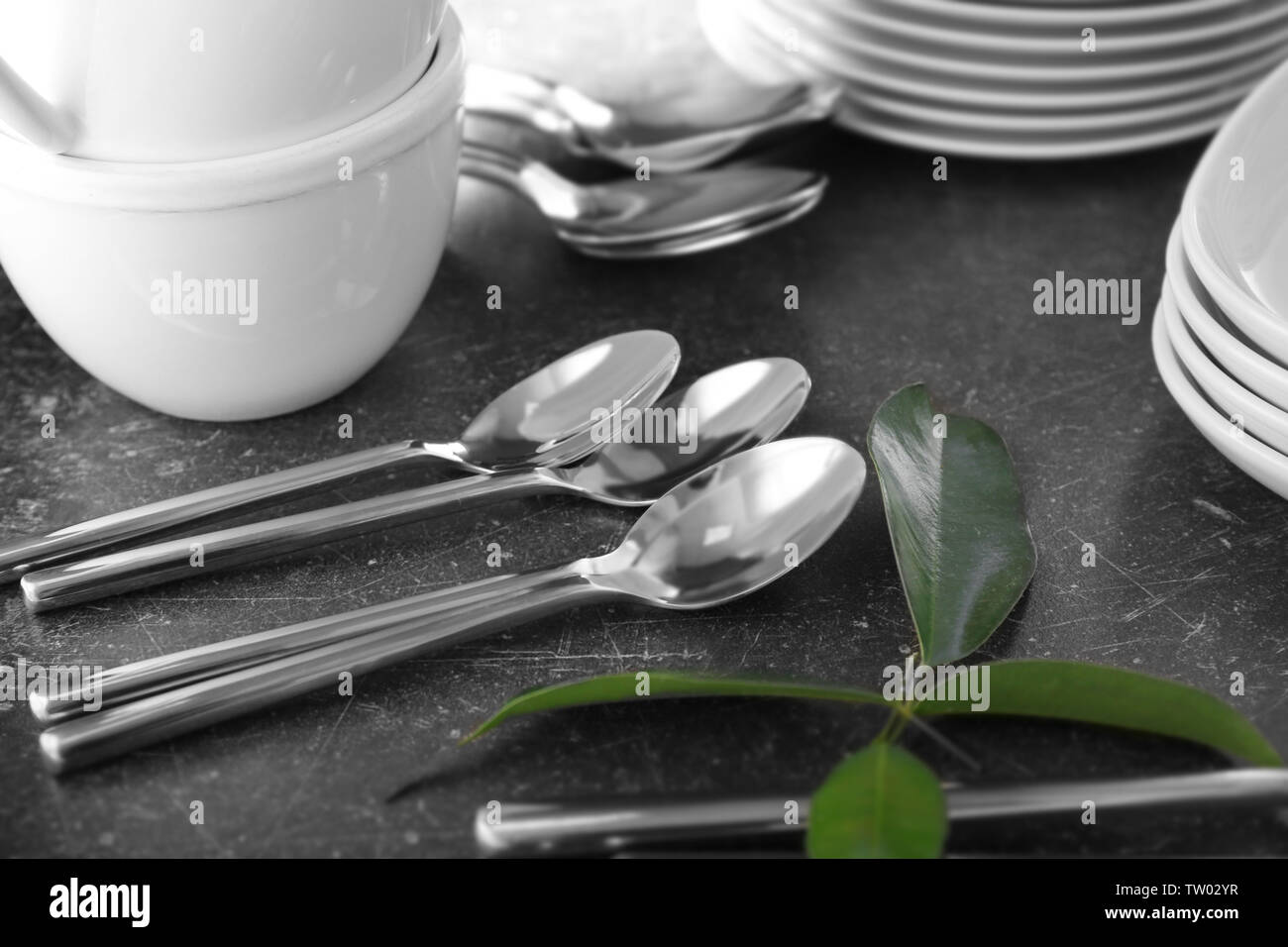 Cutlery set with plates on gray table - Stock Image