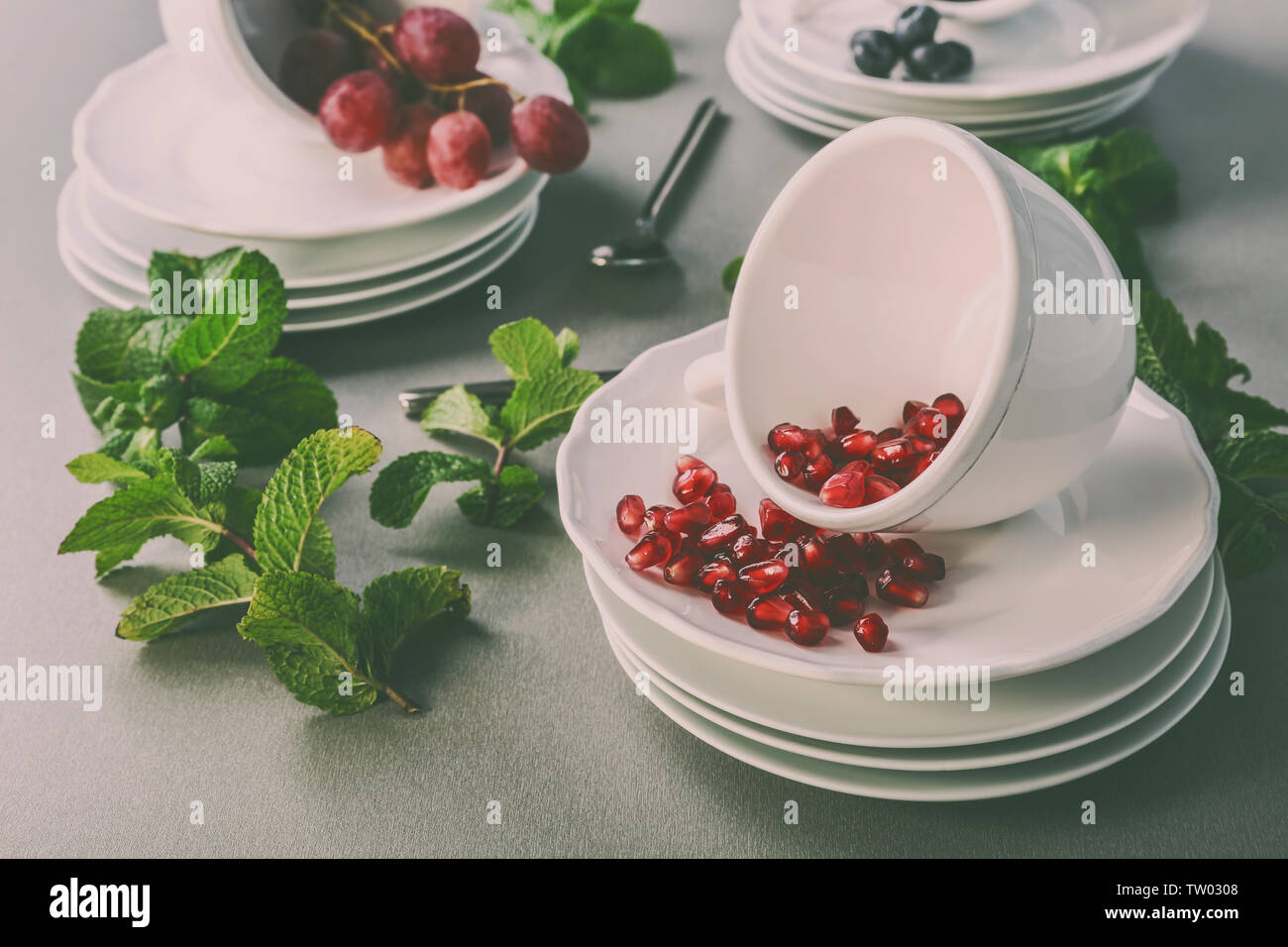 Cups set with grapes, bilberry and garnet on gray background - Stock Image