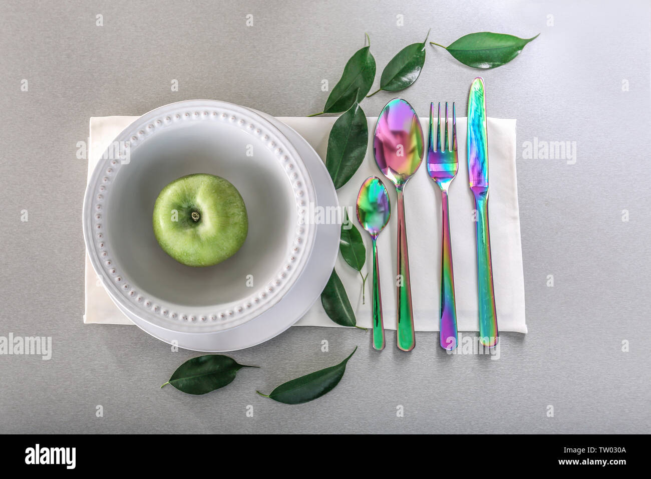 Cutlery set with plates and green apple on gray background - Stock Image