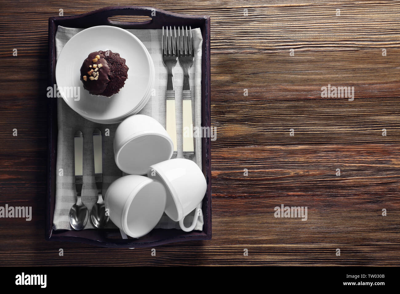 Cups set with tasty chocolate cake, on wooden tray - Stock Image